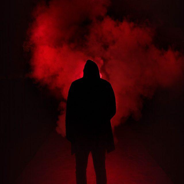 Dunkle Gestalt mit rotem Dampf im Hintergrund