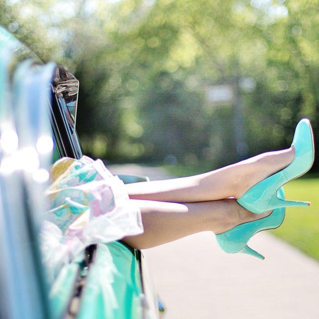 Frau steckt türkise High Heels aus dem Autofenster