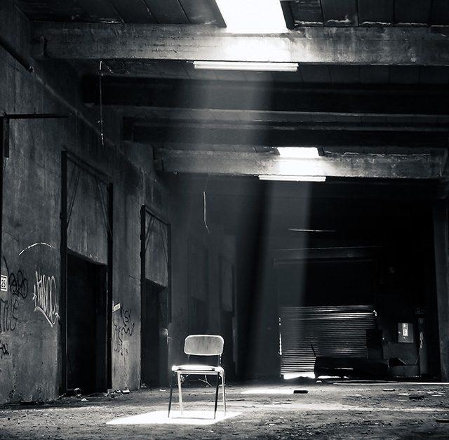 Leerer dunkler Kellerraum mit Stuhl in der Mitte